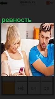 Девушка смотрит в телефон, а парень высказывает ревность по отношению к девушке