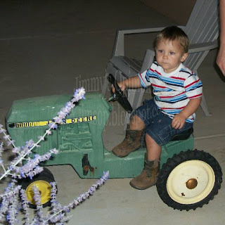 Grandson Benjamin sitting on a toy John Deere tractor wearing his cowboy boots
