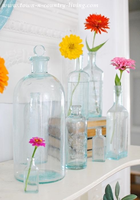 Zinnias in vintage glass bottles make perfect summer mantel decor.