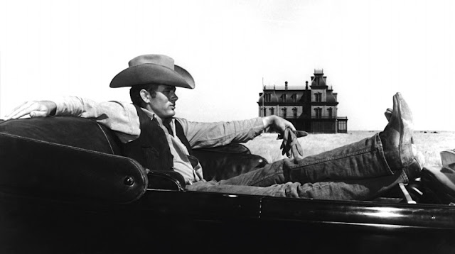 Jett (James Dean) sitting in the car in front of ranch house