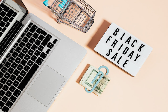 "A  laptop, a ""Black Friday Sale"" sign, cash, and mini shopping cart shot flatlay-style against a peach surface."