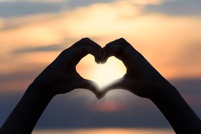يصنع بيديه، بيديها قلب حب عند الغروب