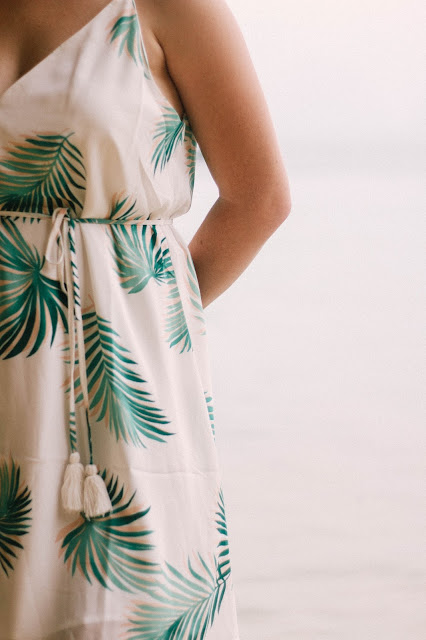 Fashion and Travel Blogger GlobalFashionGal (Brianna Degaston) wearing a palm tree leave printed dress with white tassels in Railay Beach, Thailand.