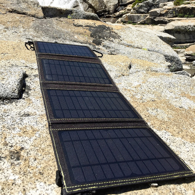 Sunjack 14W Portable Solar Charger on the rocks charging