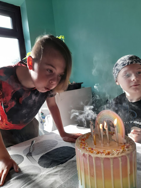James leans on a table blowing out the candle. Smoke drifts towards him