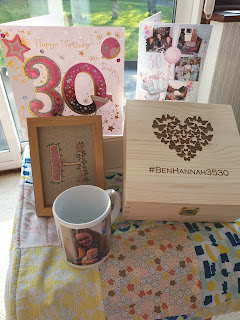 A homemade patchwork quilt with a wooden box with butterflies in the shape of a heart and the words #BenHannah3530 on it. There are several 30th birthday cards and a photo mug next to the box.