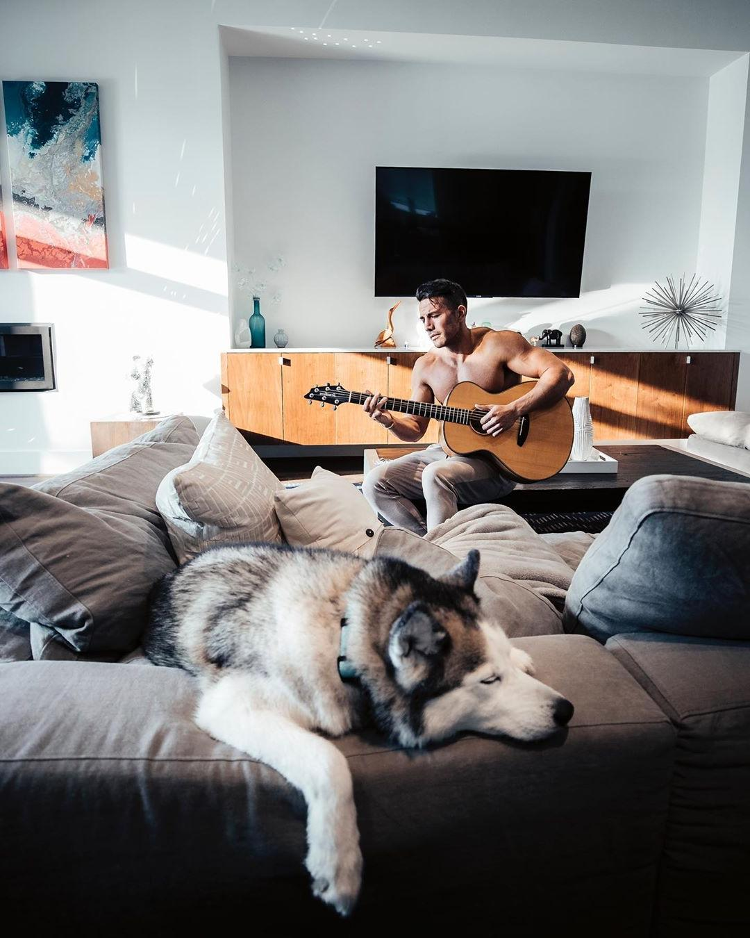 hot-shirtless-fit-guy-playing-guitar-dog-listening-sleeping-sofa