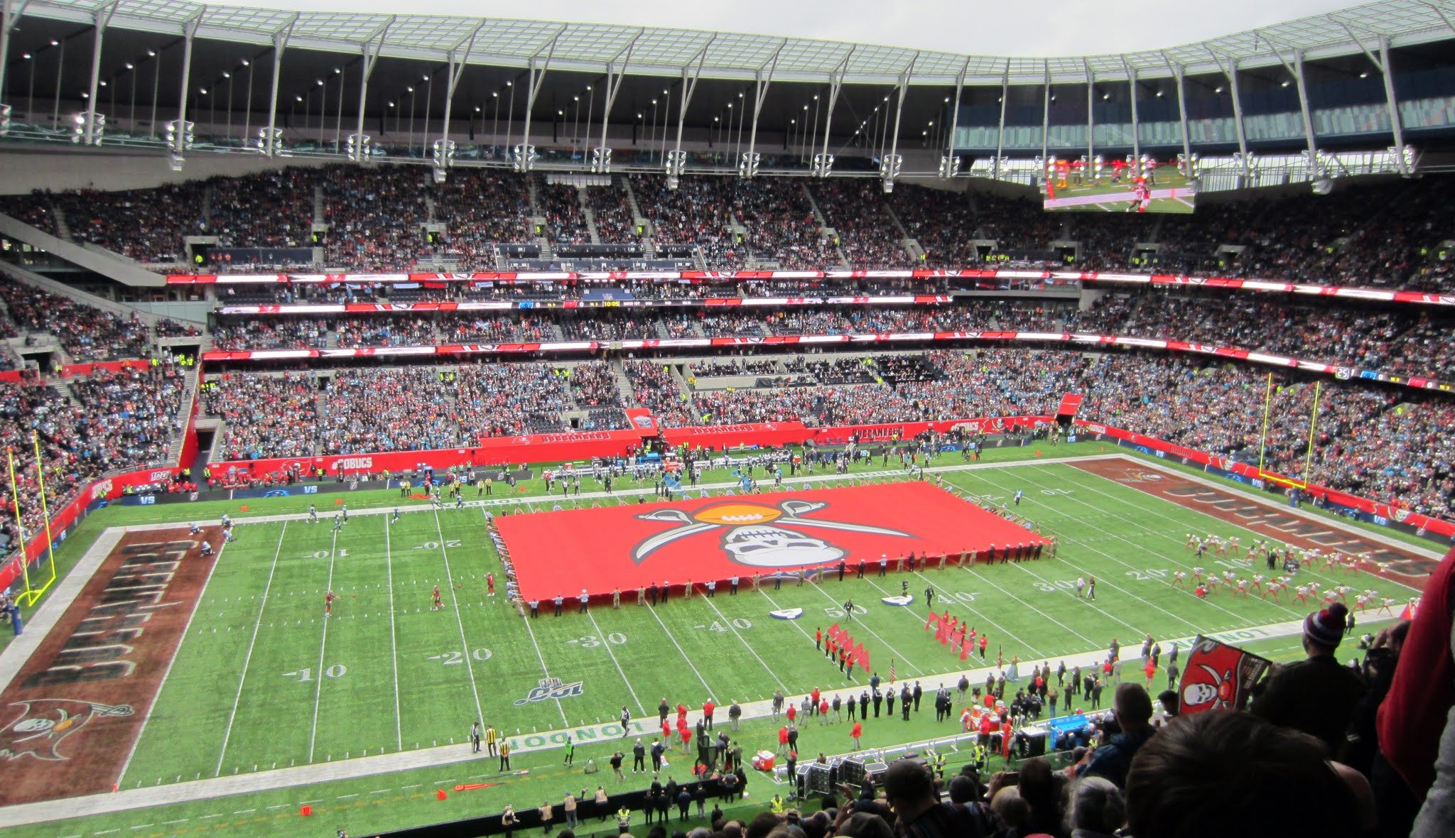 Large Tampa Bay Buccaneers flag covers the field at Tottenham Hotspur Stadium