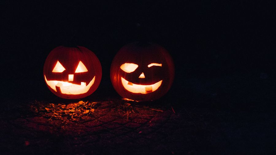 two carved pumpkin heads glow in the dark