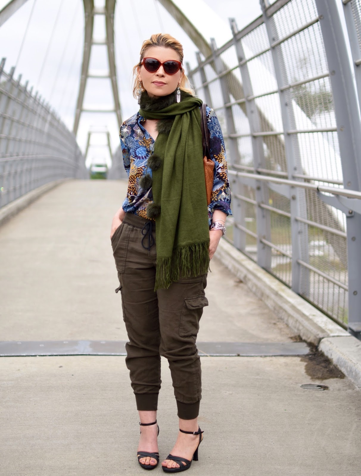 styling slouchy cargo pants with a floral blouse, pompom scarf, and ankle-strap sandals