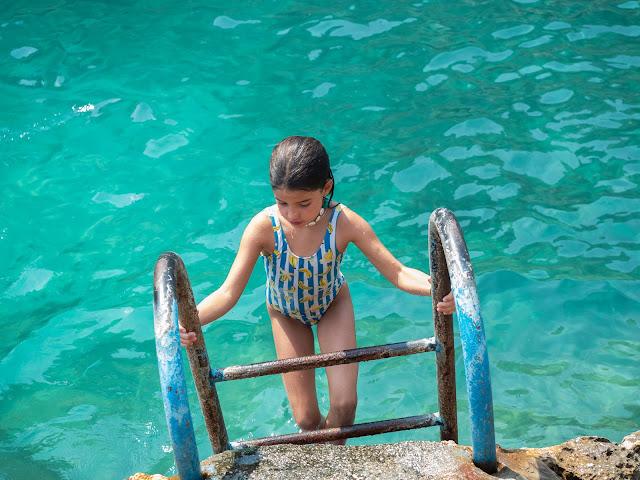 Niña saliendo del mar turquesa por una escalera anclada en la roca.