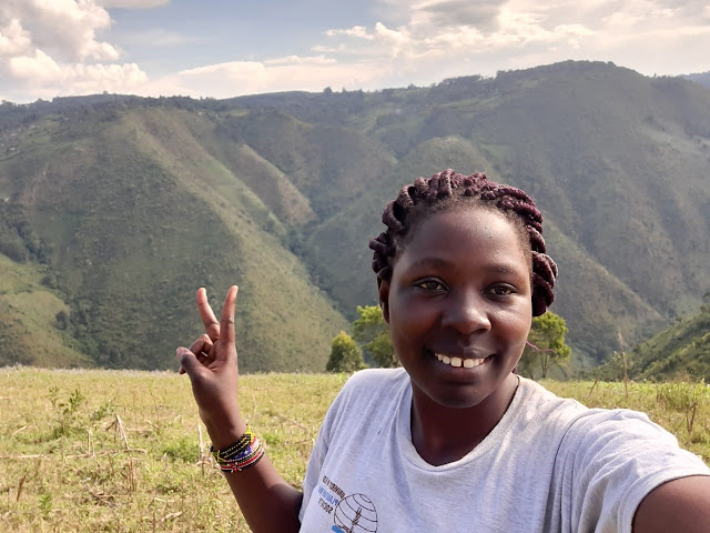 Melvine stands in front of some of Nandi County's slopes, holding her fingers in the peace sign