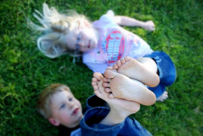 feet are in focus with kids laying in grass