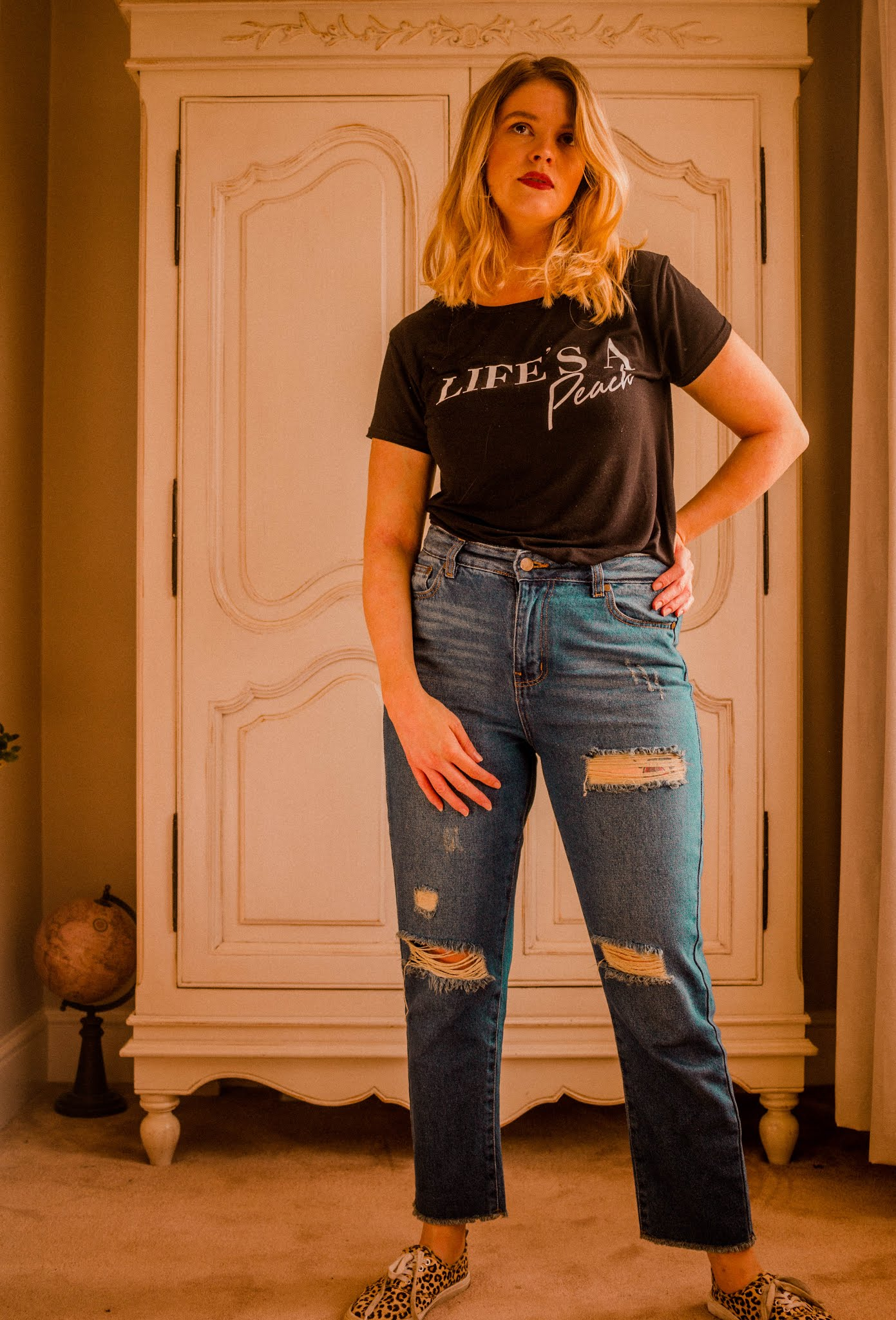 blonde girl wearing femme luxe outfit. Casual blue ripped denim high waisted jeans and black and white printed graphic tee