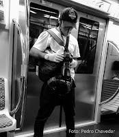 Fotógrafo segura equipamento de fotografia, dentro de vagão de metrô