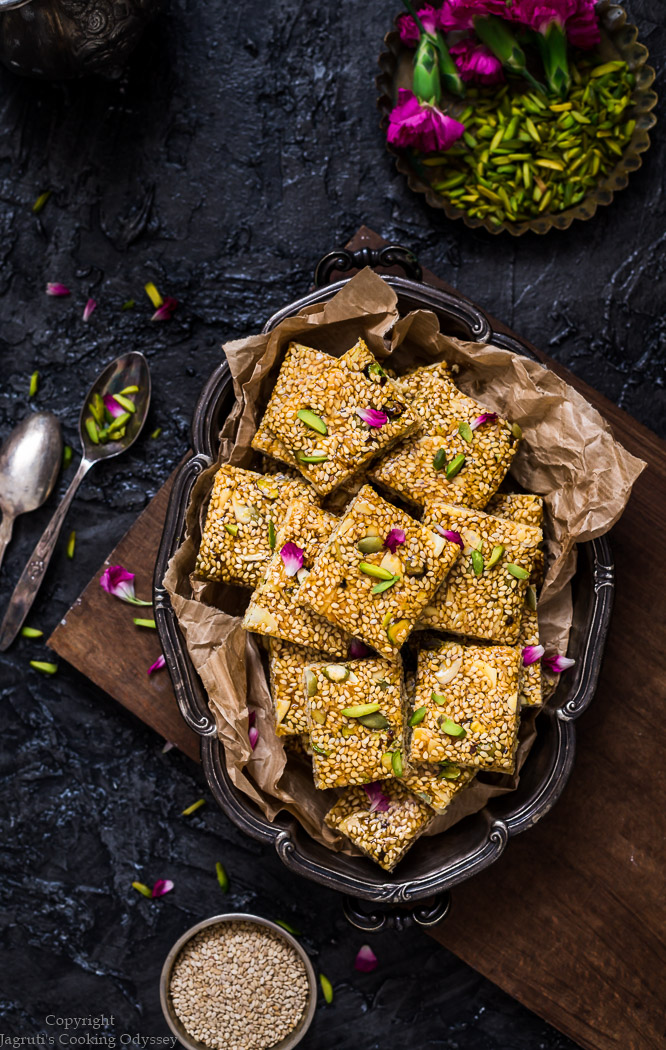 Til chikki served in a tray, garnished with pistachio nuts and rose petals