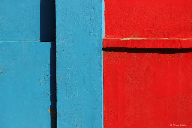 A Minimalist Photograph of a Wall with Two primary colors, blue and red.