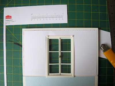 Cardboard template on top of a Lundby Smaland dolls' house wall with French doors.