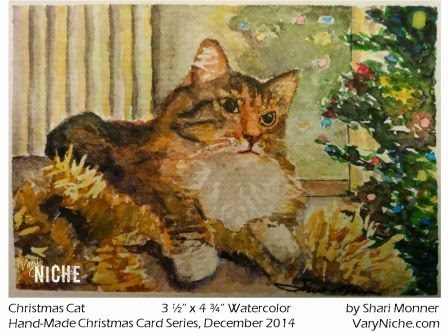 Watercolor Painting of long haired calico cat laying on gold garland in front of a christmas tree. by Shari Monner, VaryNiche.com