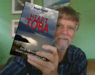 Nigel Foster holds his new book Heart of Toba