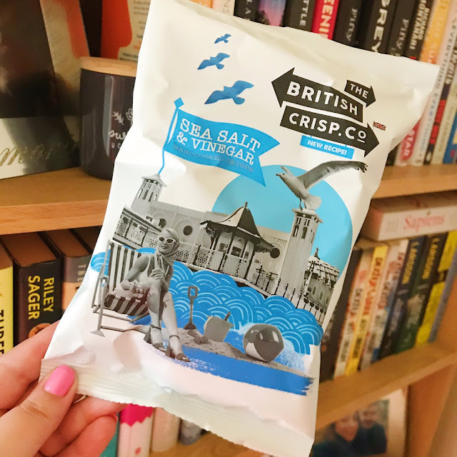 Sea salt and cider vinegar crisps held up in front of bookshelf