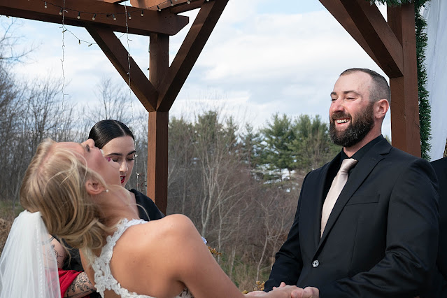 Candid of Bride bending backwards laughing and Groom smiling at the alter during ceremony Magnolia Farm Asheville Wedding Photography captured by Houghton Photography