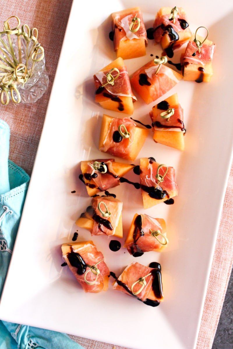 Top view of proscuitto wrapped cantaloupe on a white plate with a pink background.