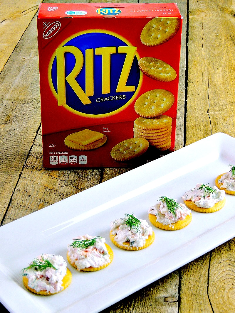 Smoked salmon appetizer bites on a white tray on top of a wooden table with a box of RITZ crackers behind.