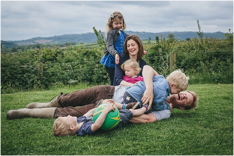 A family rolling on the grass and laughing