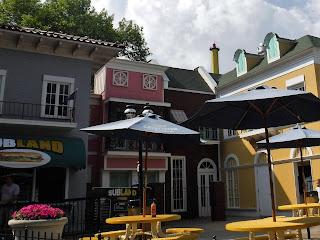 a sandwich restaurant with patio tables and umbrellas at Adventureland in Altoona Iowa