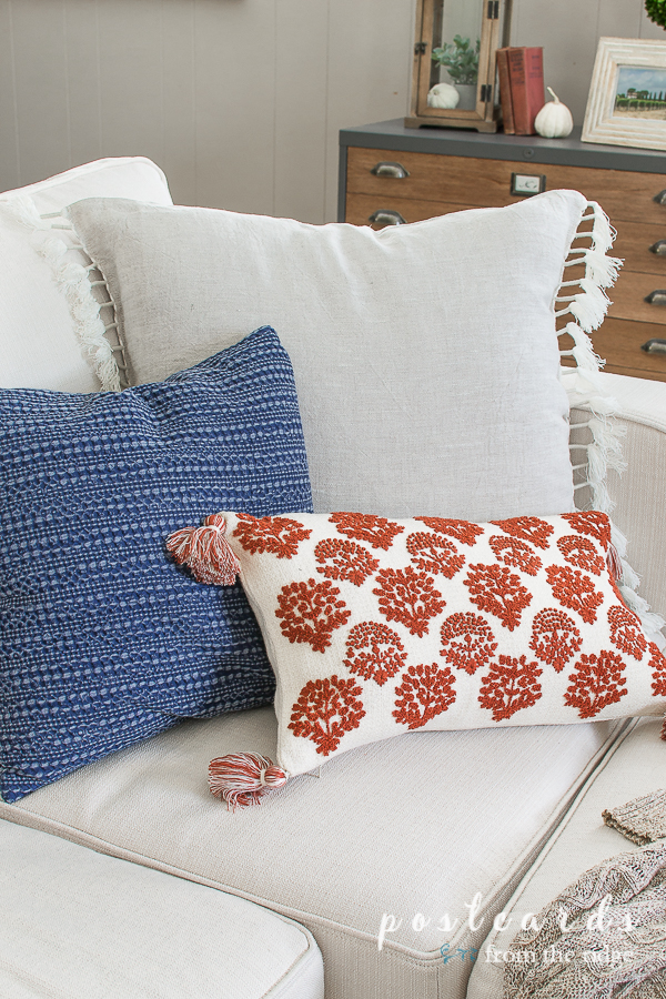 orange and cream pillow and blue pillow and linen pillow with fringe on an off white sofa