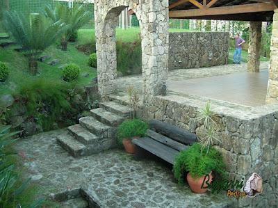 Piso de pedra moledo, com espessura de 10 cm a 15 cm, com a escada de pedra, o muro de pedra e o pórtico de pedra em sítio em Mairiporã-SP.