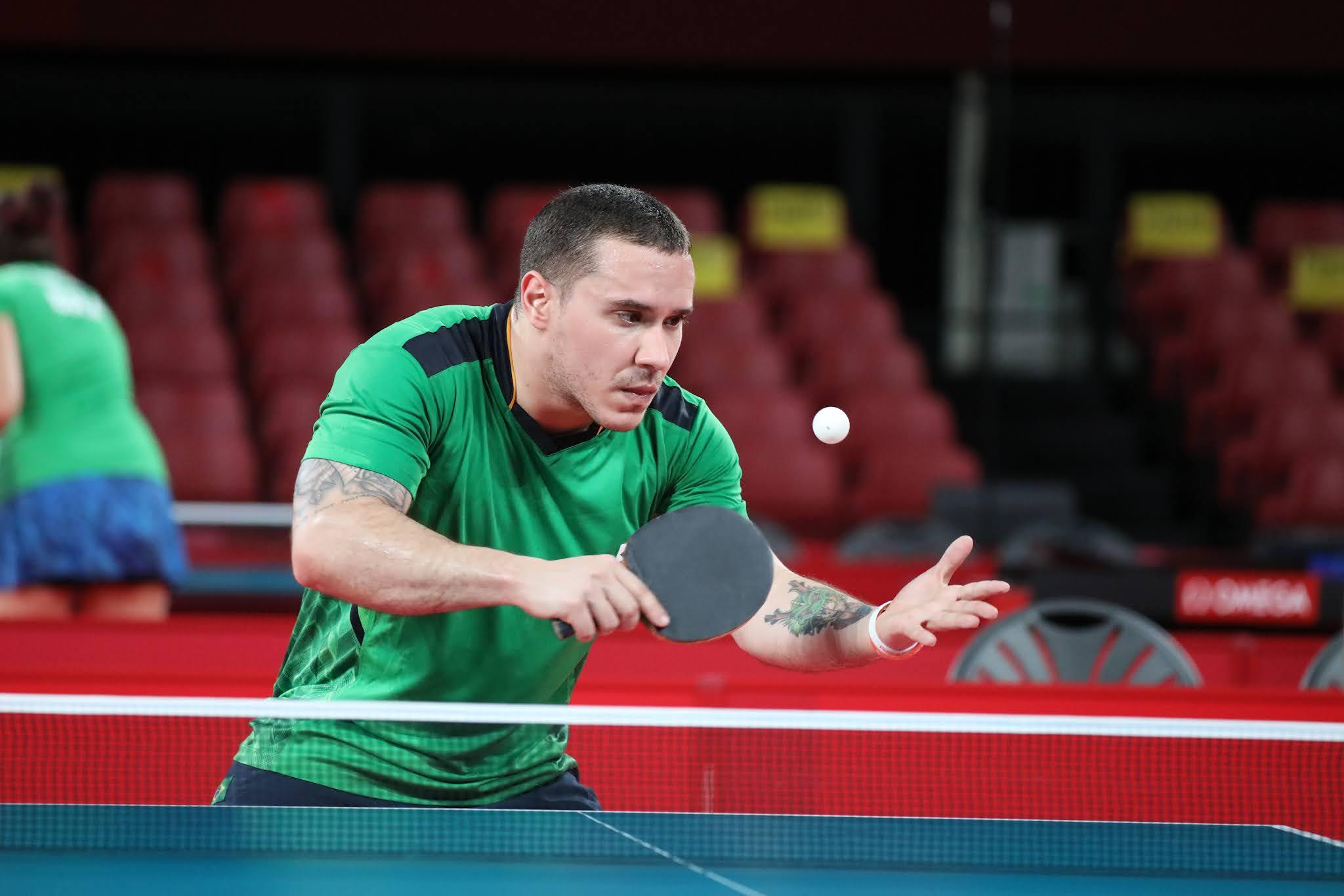 Carlos Carbinatti executa um movimento durante treinamento; ele veste verde e está com a raquete na mão esquerda