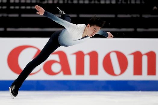 Vincent Zhou executando um salto. Ele usa calça preta e camisa azul em degradê