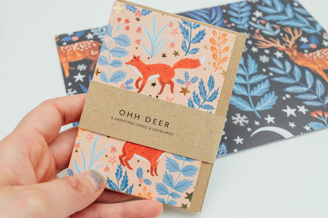 A pack of Christmas cards with foxes and a floral print all over