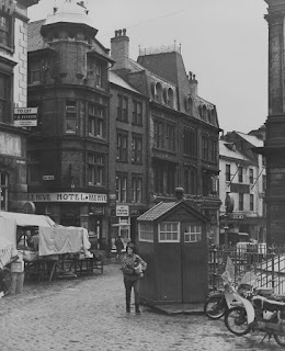A black and white photograph of a wet cobbled marketplace. A police call box is at the centre of the image with a person walking by carrying something. There is a row of shops including an old-fashioned Hotel in the background, with the rear of a covered market stall in the middle ground.