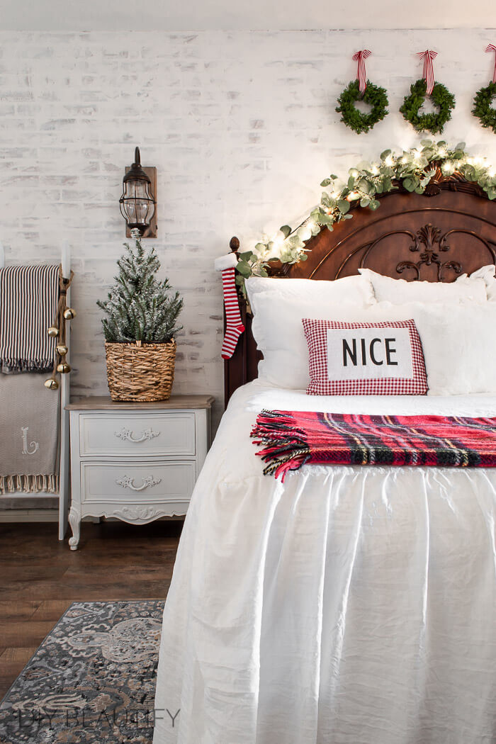 Christmas wreaths and plaid throw in bedroom