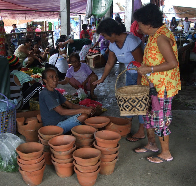 women buying clay pots at the market