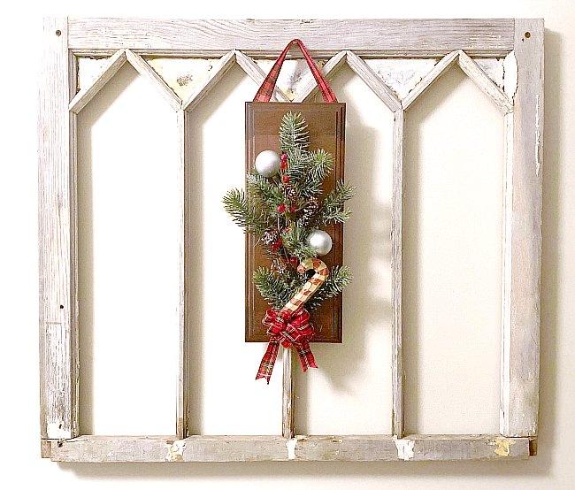 Cabinet door wreath on a vintage window
