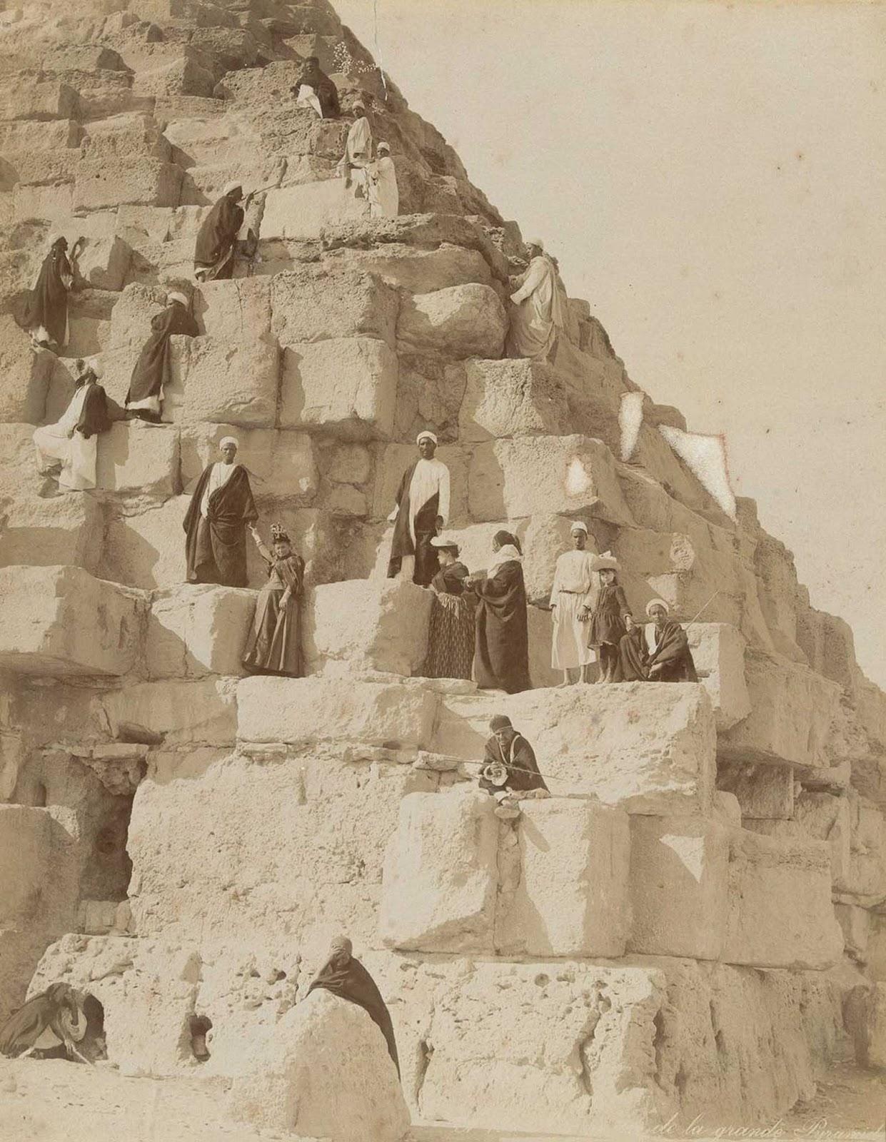 Turistas europeos y guías locales suben a una de las pirámides de Giza.