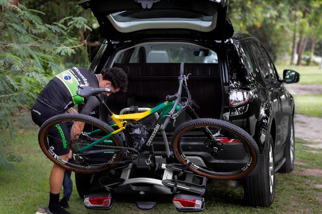 Henrique Avancini ajusta sua bicicleta em seu carro, o Discovery Sports