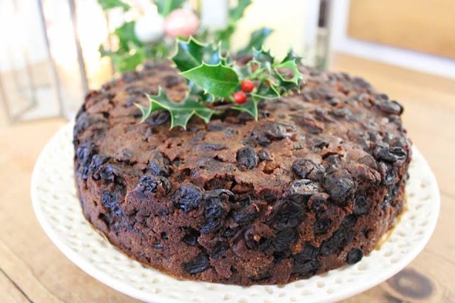 Fruit Christmas cake topped with a holly sprig