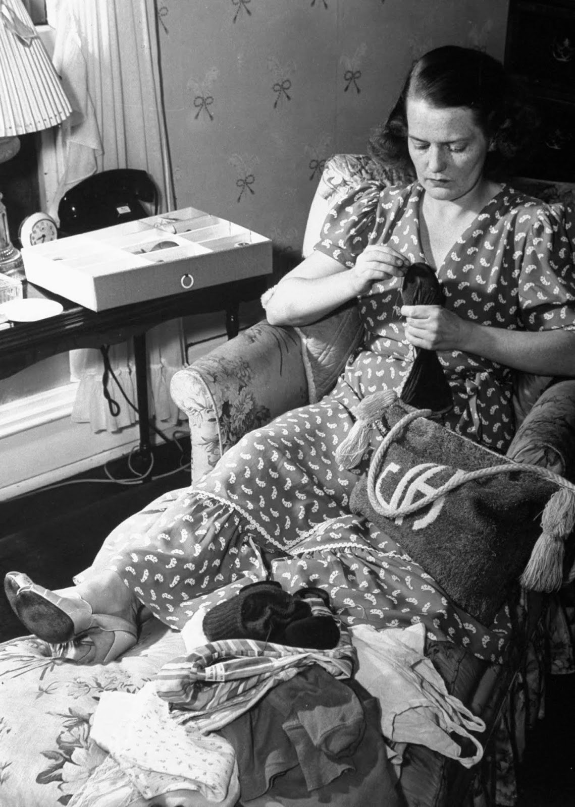 Jane mending a pair of socks as she lounges in bedroom while listening to her favorite jazz records during her leisure hours (time with out kids).