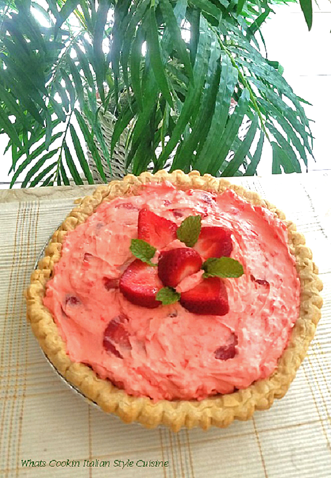 this is a strawberry cream  pie filled with strawberries, whipped cream and a jello pudding filling. Topped with a flower arrangement pattern using strawberries and mint leaves on top. There is also a large green plant behind the pie