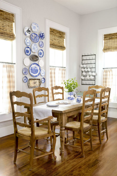 Farmhouse style dining room in a charming cottage. Blue and white plates adorn the wall, ladder back chairs cozy up to the farm table, and check curtains decorate the windows. #diningroom #farmhouse #cottage #homedecor #decoratingideas #countryliving