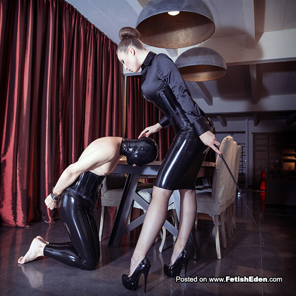 Riding crop Dominatrix wearing black latex mini-skirt with her black latex hooded slave