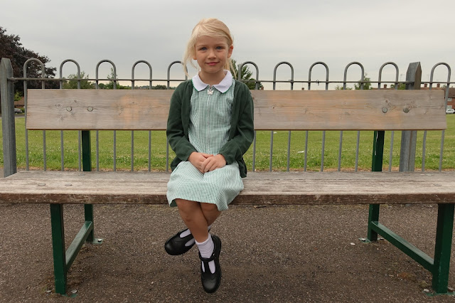 A young girl in a green checked school summer dress, green cardigan, white socks and black t bar shoes sitting on a park bench.