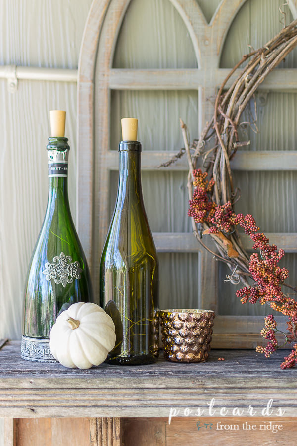 wine bottles with small white pumpkin and mercury glass votive holder