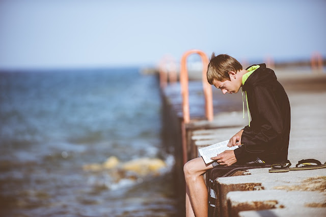Membaca buku di tepian pantai