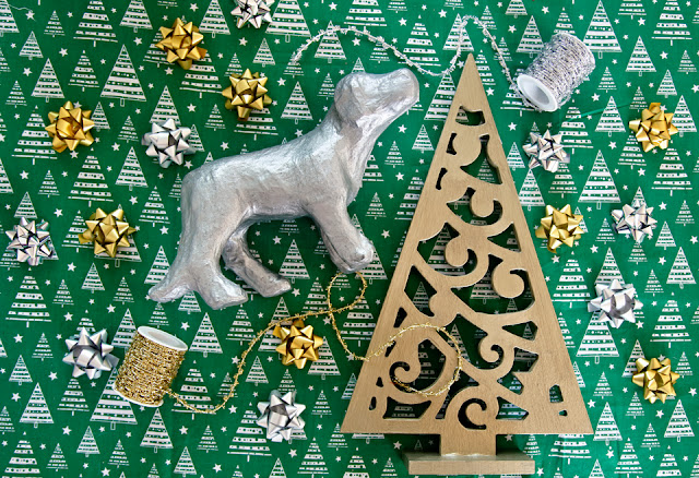 Metallic silver painted dog ornament and gold tree with Christmas decorations